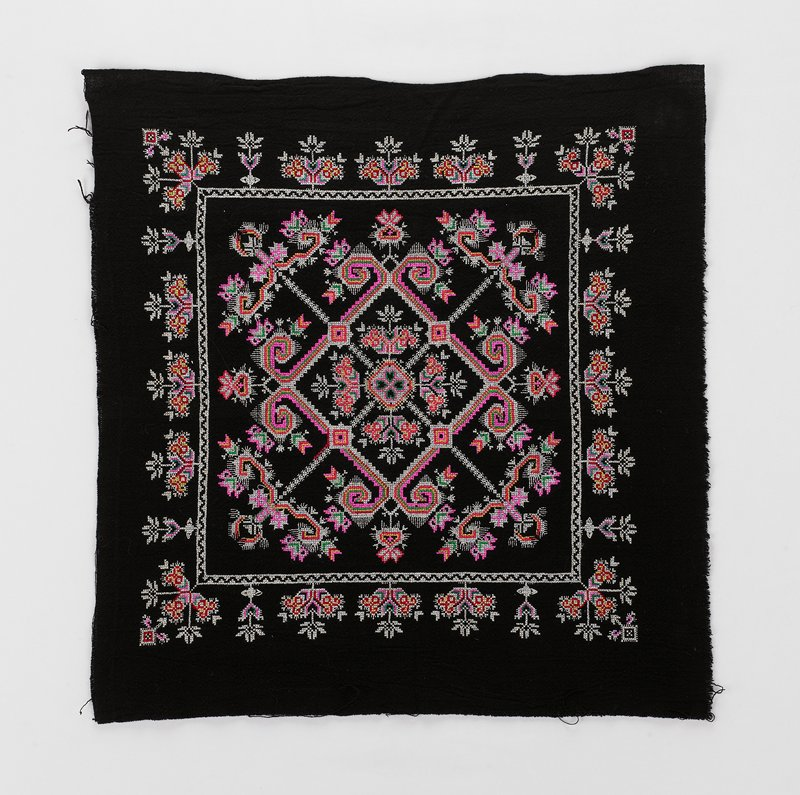 white, pink, red, green and yellow discontinuous supplementary weft patterning on black field; thin central cross intersected by a decorative multi-band square, larger white square around border with floral designs along all sides
