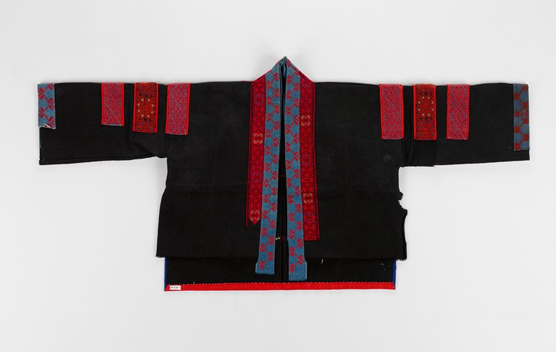 black coat with red and blue embroidered bands on collar; also three embroidered bands on each shoulder; blue and red embroidered bands on cuffs; large embroidered patch top center on back; embroidered band on back at hem