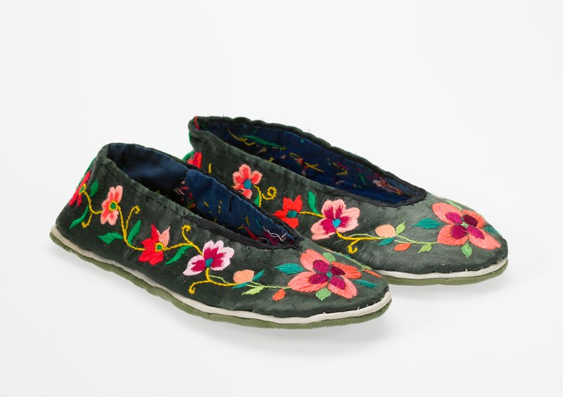 dark grey uppers, green soles sewn with white thread throughout; decoration includes large orange and maroon flower on front Gelatin followed by four sets down each side