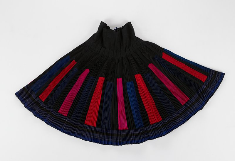 black ground with cloth waist band and striped band around hem of; blue and thin lines of white, red, brown; main field of skirt has vertical rectangular areas in red, blue and pink