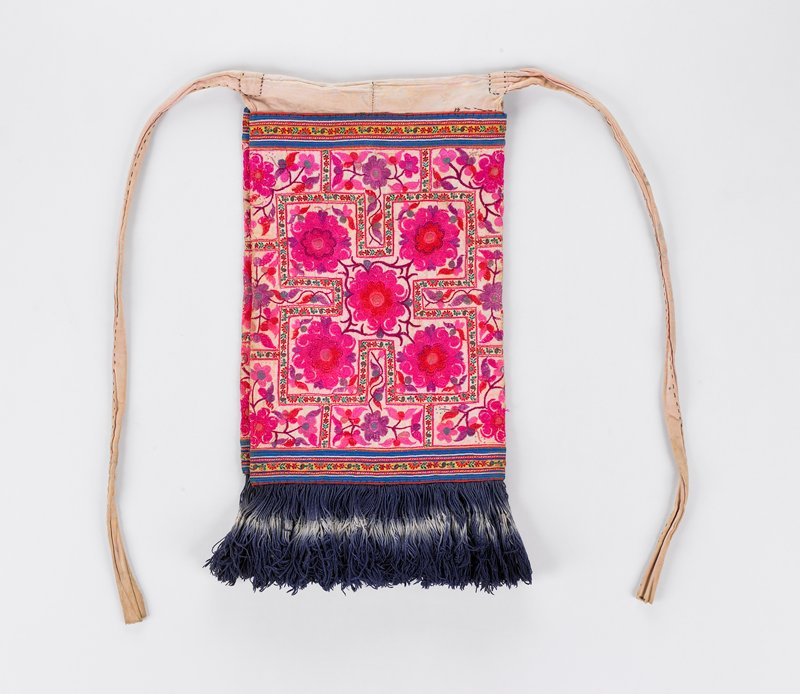 rectangular cloth folded in middle; when folded, the top of each flap is embroidered with fuchsia flowers; back side is made of light pink fabric with floral print; both flaps have blue tassels; tassels are white in the middle