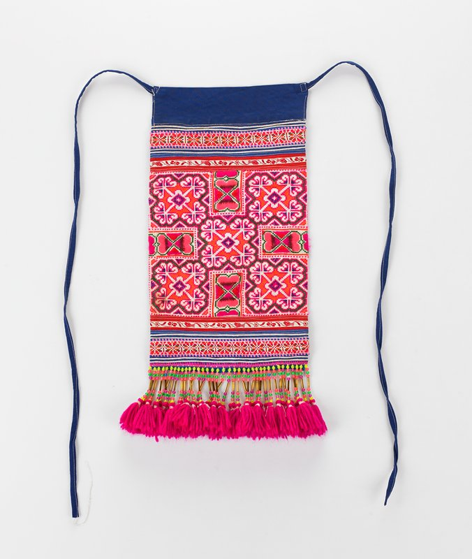 apron with fuchsia tassels attach by yellow, pink and green beads; blue ties and blue band at top; main body embroidered in fuchsia orange and green; back of apron from white fabric with printed pink and red flowers