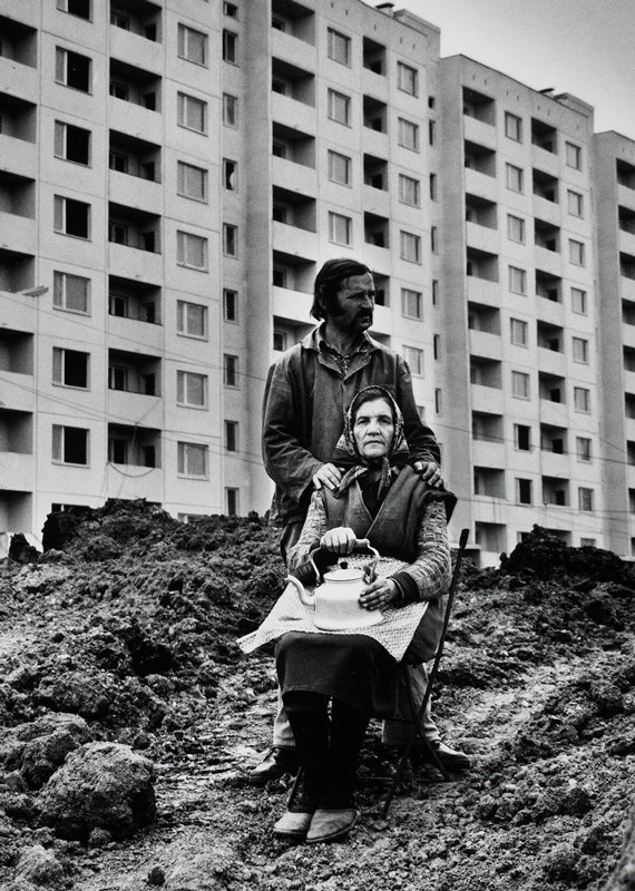 black and white; man and woman on dirt pile in front of building; man standing, woman seated, holding tea kettle
