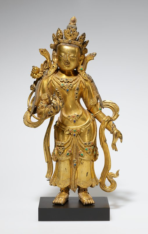 standing gilt bronze figure in contraposto position, proper left hand open at side, right hand held in front, hanging jewelry highlighted by inlaid stones