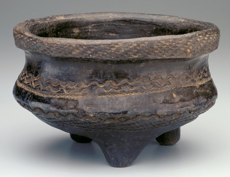 tripod bowl, thick walled black earthenware; round base and concave body with wide lip; three bands at outer lip, below hip and within concave body; body band of two wavy lines above a thinner and closer wavy line; lip and hip band have rope like designs with hip having a wavy line at top