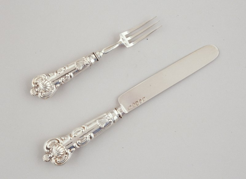 rounded knife blade; 3-pronged fork; each handle has same design on front and back which includes a scallop-shape at top and bottom; box is red with brown lining