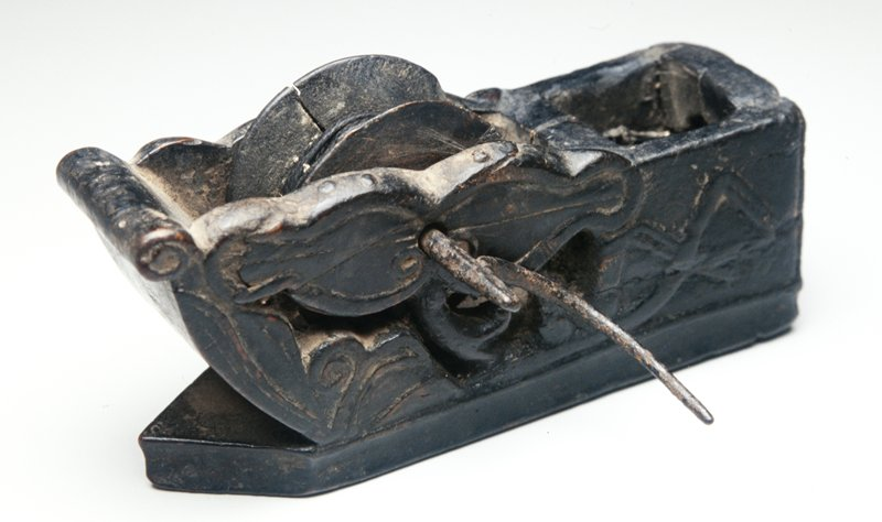 ink well and hand operated wheel with string wrapped around wheel and lead through inkwell; set in wood block carved with pierced design of open flower; wheel, string and stop entact; two metal feet at one end