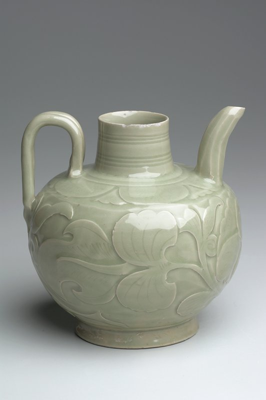 stoneware ewer with celadon glaze; carved around sides with a large peony flower in full bloom; globular vessel