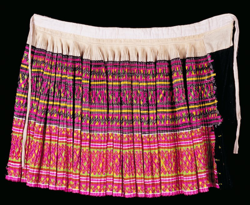 ceremonial skirt, made and worn by a Blue Hmong woman in Laos; cotton, batik with indigo, cross stitch embroidery, appliqued silk ties. Skirt is pleated and was unstitched and then repleated prior to each wearing.