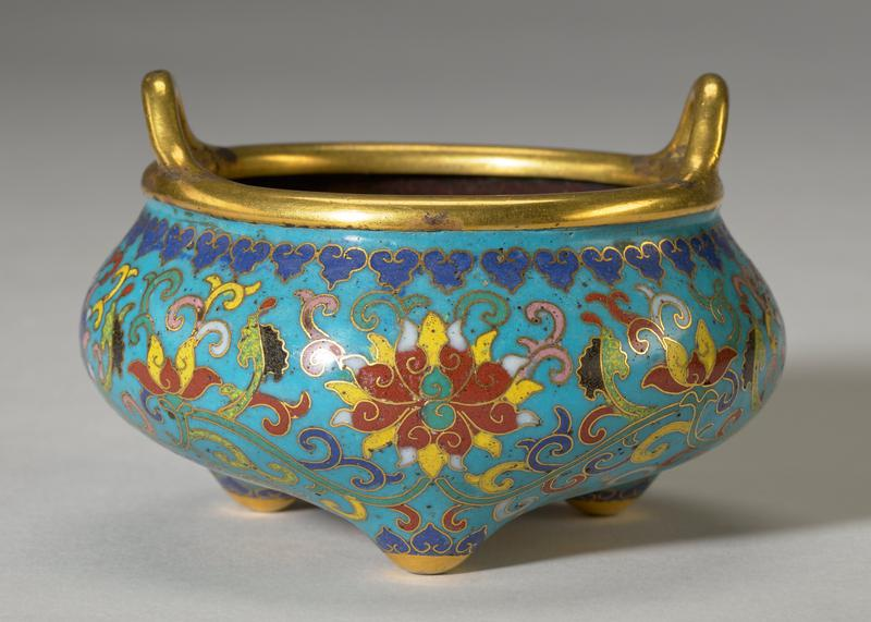 round-bodied vessel with gilt rim and two small handles; three small gilded feet; bombe sides and base decorated in red, yellow, green, black, mauve and white enamels on a turquoise-blue ground in scrolling lotus design