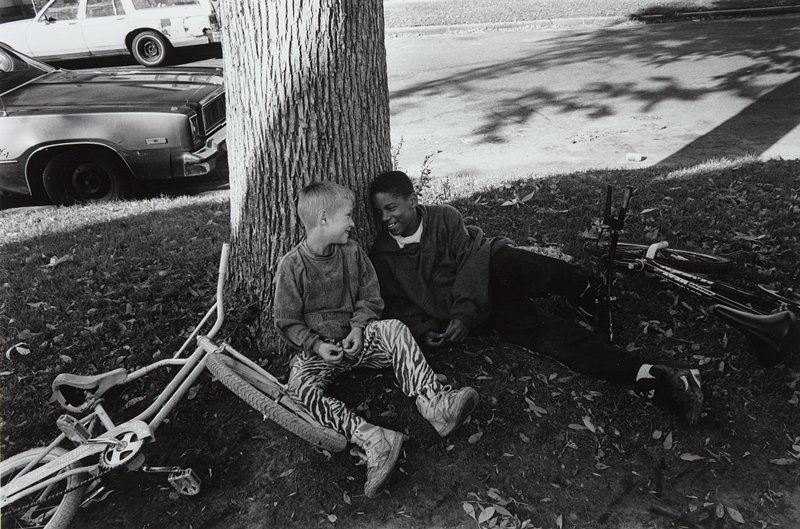 black and white photo of two seated boys leaning against tree with bicycles