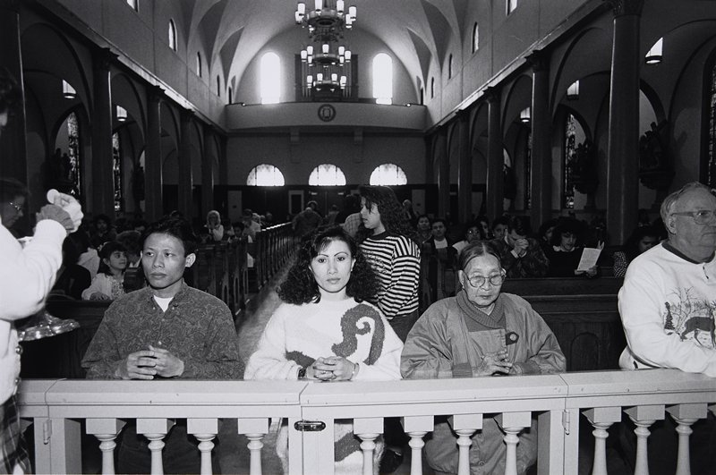 black and white photo of two men and two women kneeling for communion