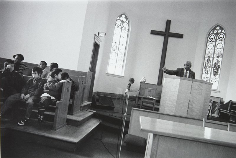 black and white photo of minister in pulpit with seven children seated off to the side