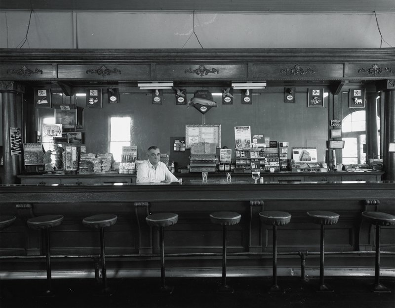 man standing behind a bar with cigarettes, bags of snack food and cash register behind him