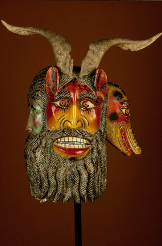 mask, wood, attached goat horns, painted orange, green, brown,red, yellow, black Triple-face mask with human face to left, dog to right and Diablo (devil) in center under goat horns. Communal beard. Iguala area.