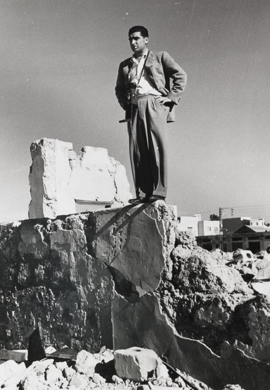 man cigarette in his mouth standing on top of a ruined wall; matted
