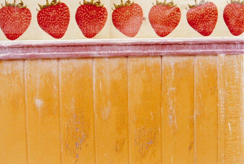 yellow wallboards with strawberries above