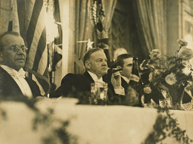 men sitting at long table; Herbert Hoover at center, holding cigar