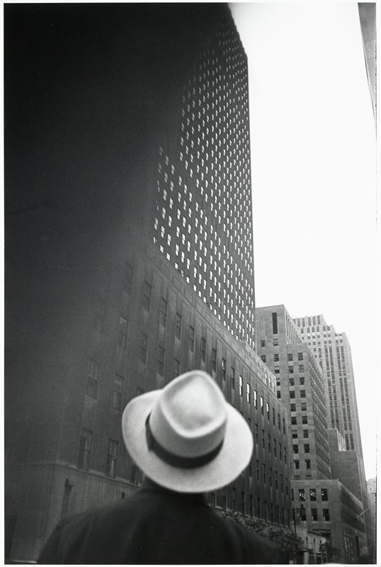 head and shoulders of a figure, seen from behind, wearing a light-colored fedora, looking up at a skyscraper