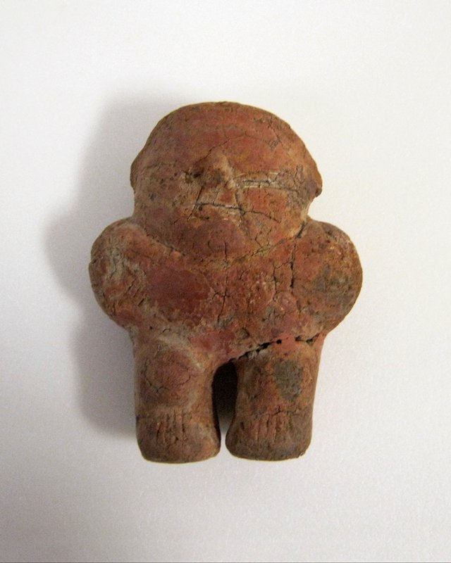 standing figure with thick legs and protruding knees; hands on hips; scattered lightly incised details