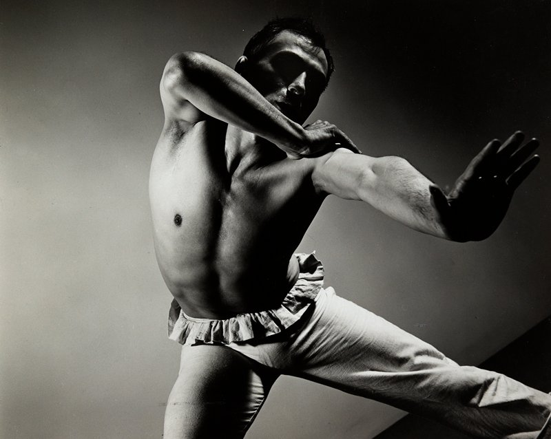 male dancer wearing pants with a ruffle at the waist; PL arm out with wrist bent and PR arm up and bent at elbow, with PR hand on PL shoulder