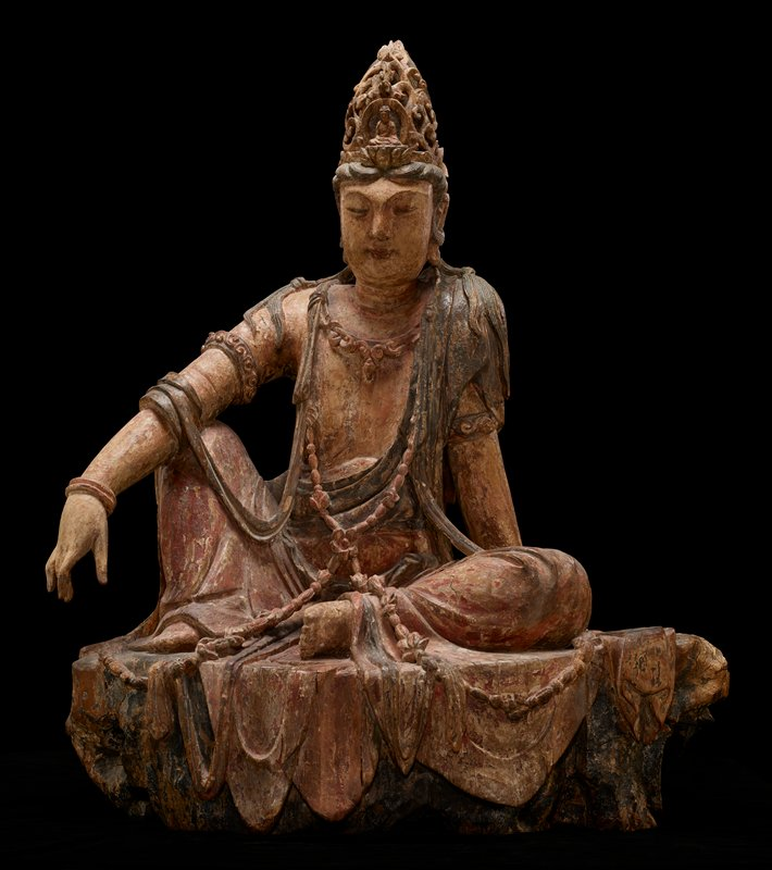Seated figure, resting PR elbow on raised PR knee, PL leg bent and on ground and PL arm behind, hand resting on ground; wearing bracelets, long necklaces and elaborate crown