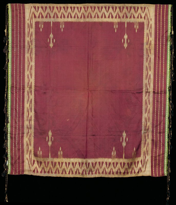 cranberry with gold patterning; green bands at 2 opposite edges with black fringe tassels