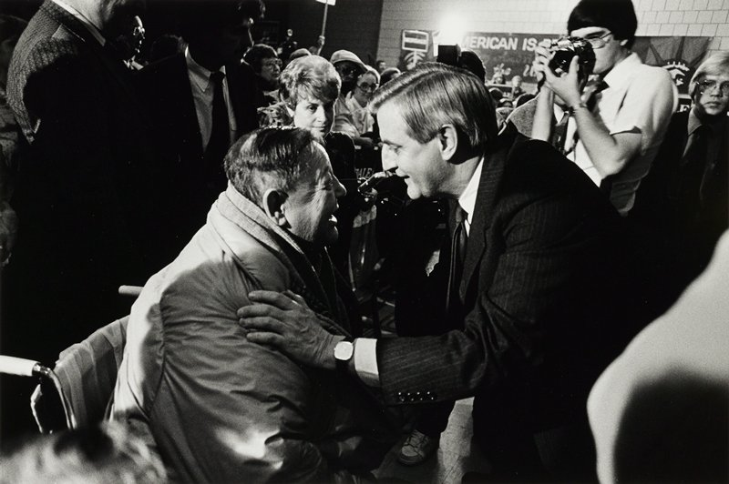 Walter Mondale right speaking to seated man left while being photographed