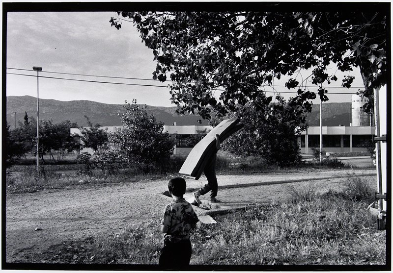 man carrying two mattresses, boy looking on