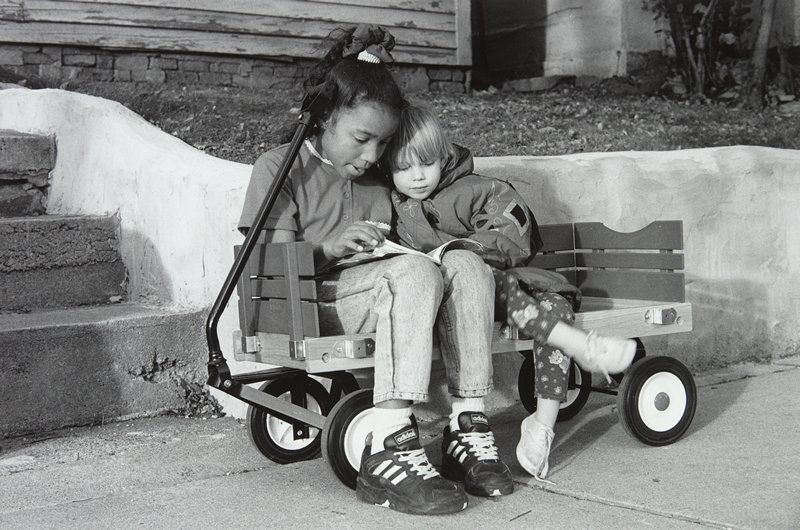 "black and white photo of two girls seated in wagon in front of steps, reading; from ""Frogtown Series #97"""