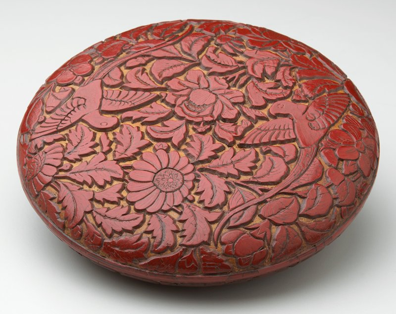 squat, round, red lacquer covered box with black interior and bottom; cover decorated with flowers, foliage and 2 birds with long tail feathers; sides of box with flowers and foliage