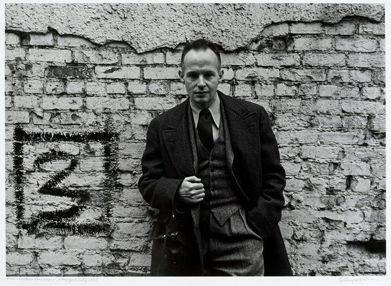 man wearing three-piece suit and coat; standing against brick wall, PR hand holding coat edge at stomach, camera suspended from arm by case strap