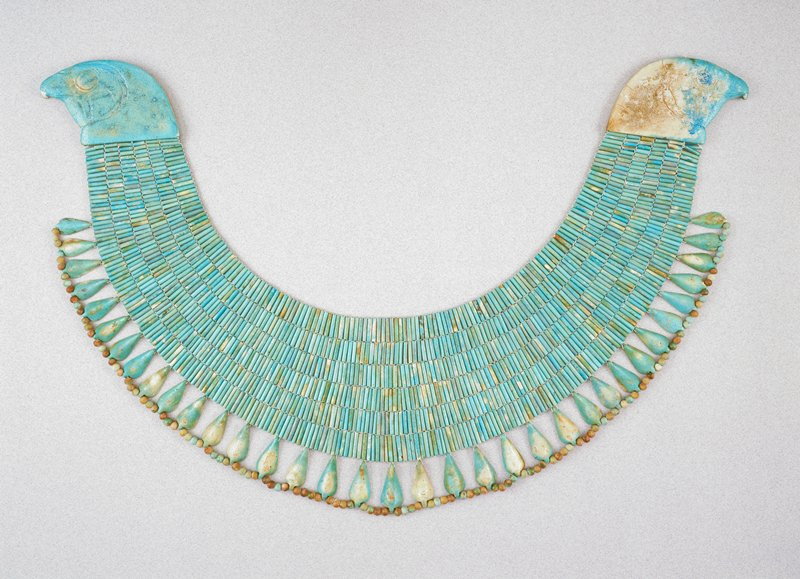 broad collar of blue faience beads, an extraordinarily large example of funerary jewelry typical of the middle kingdom; blue glazed faience. Both heads generally cracked and chipped at beak.