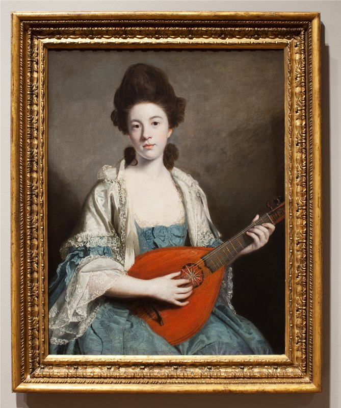 Portrait shows Mrs. Froude seated, wearing a blue dress, quilted with bows in front, a white satin mantle trimmed with lace over her shoulders, playing a mandolin.