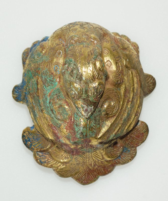 seated bird with head turned toward tail and rested on back; long, curling feathers on wings and tail; details etched into surface; polished gold color with some blue, green and red (azurite, malachite and cuprite) encrustations