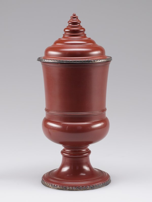 Ceramic-stoneware with silver gilt mounts around foot and edge of lid. Finial of lid chipped. Campana shaped goblet supported on a knobbed stem.