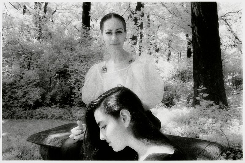 woman with hair pulled back, wearing a blouse with full sleeves, seated on a stone bench; profile of a young woman's head, from PL, with long dark hair, in front of woman; trees behind