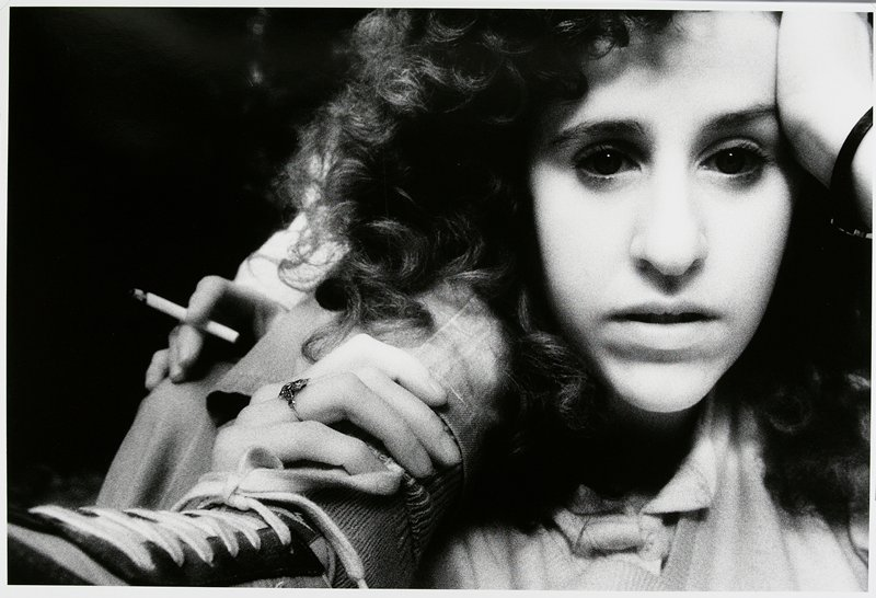 woman with long curly hair at R, resting her PL hand on her temple, her PR hand clutching a figure's PL ankle; PR knee of figure visible behind foot; PR hand holding a cigarette resting on knee; matted