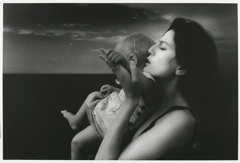 profile from PL of woman with dark hair holding a baby with blonde hair, with the baby's PL shoulder under her chin; woman holds baby's arm in her PL hand, in front of baby's face