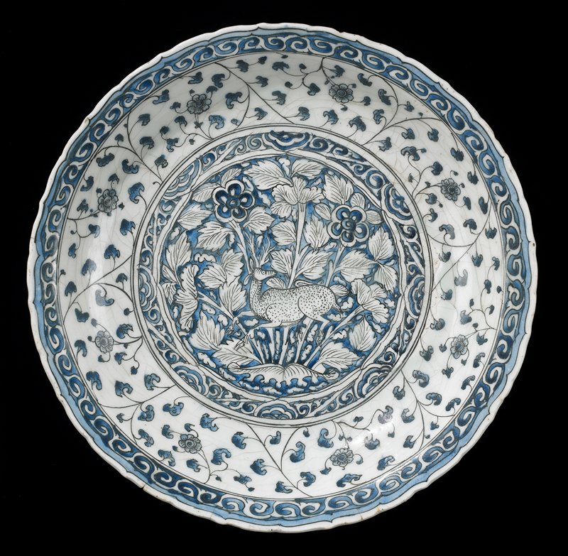 Dish, Meshed ware, Safavid Dynasty, early XVII Century. White earthenware with underglaze blue and black decor. Central medallion reserved in white and painted in outline black on a blue ground with stag leaping in foliate landscape within border of scrolling tendrils.