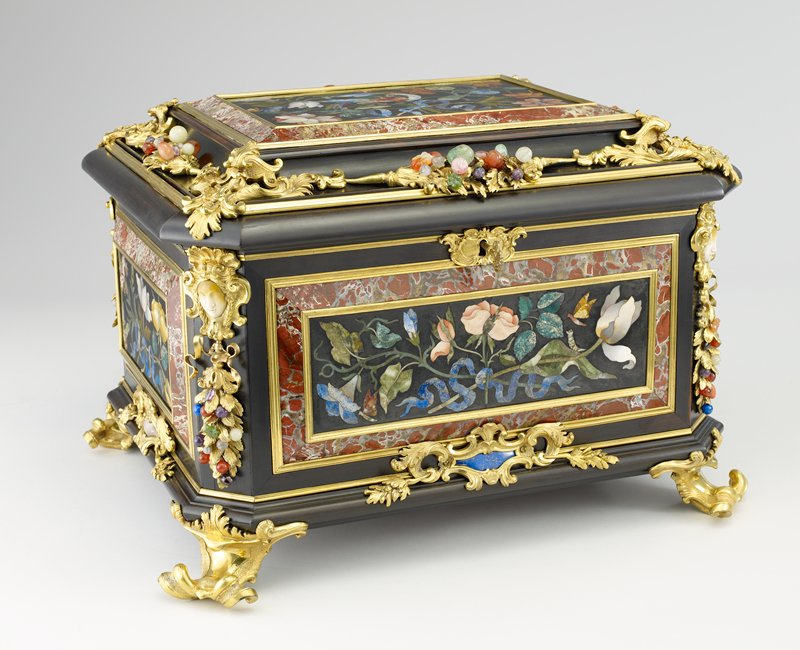 oak veneered with ebony, mounted on all four sides and lid with rectangular slate plaques inlaid with lapis, agate, and marble; design of flowers tied with ribbons, a parrot and butterflies, ormolu leaf sprays on sides, corners have female masks in agate with ormolu ribbons