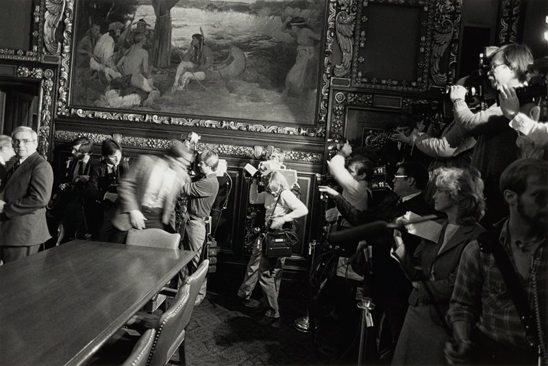 journalists and photographers in front of painting of Native Americans gathered by a river