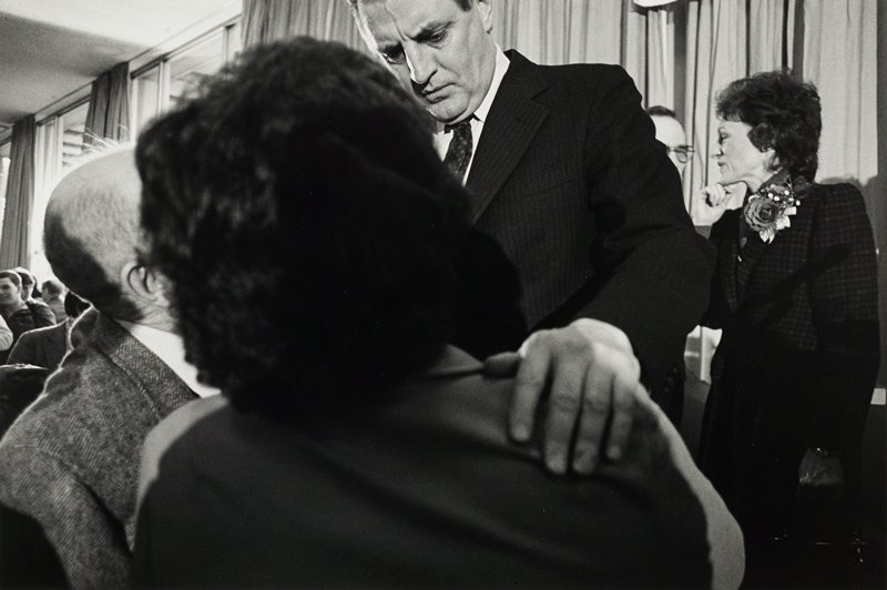 Walter Mondale talking with a man and woman; Joan Mondale, back right, with hand to her chin