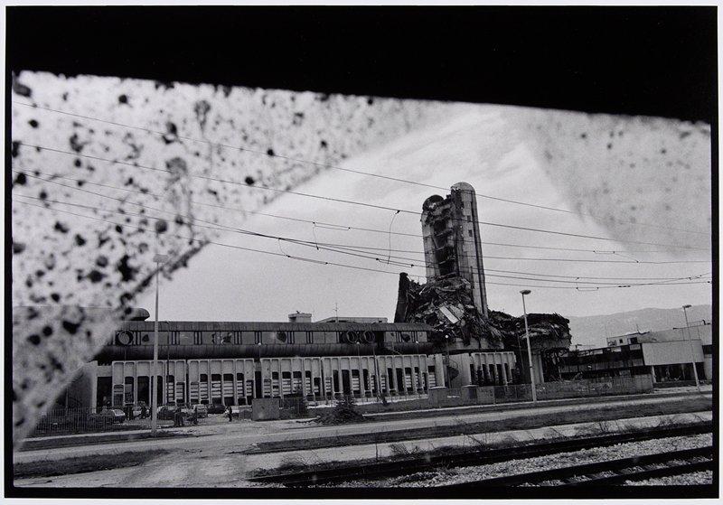 damaged tall building seen through muddy window