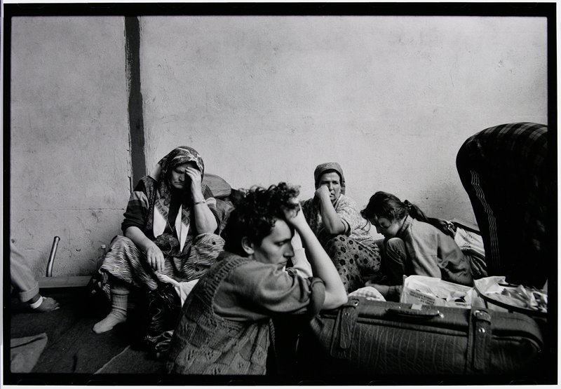 four seated women with elbows up and hands holding head