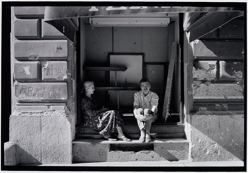 older couple sitting in destroyed building entry