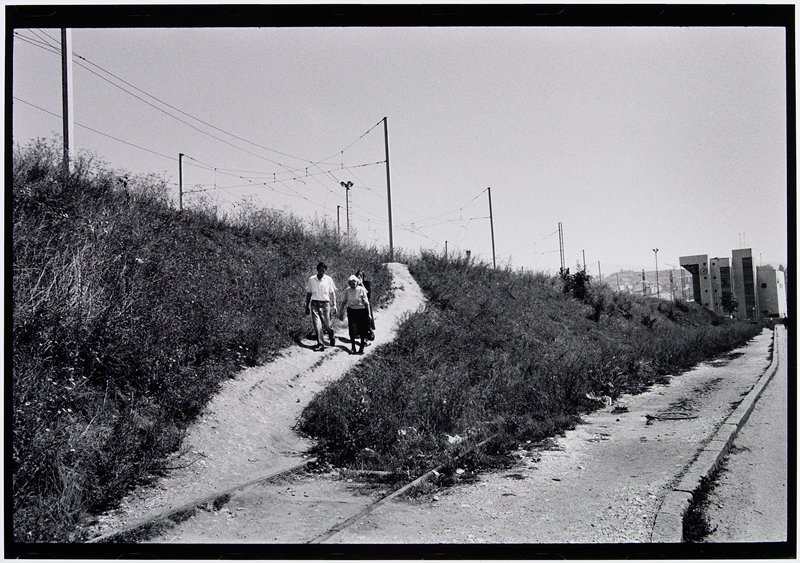 three people walking down a gravel path to road