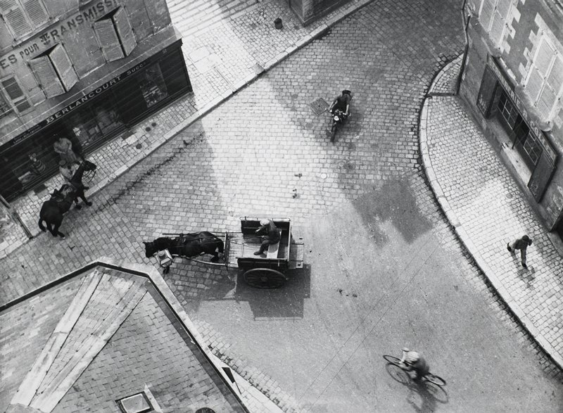 overhead view of cobblestone street corner with horse and cart turning left