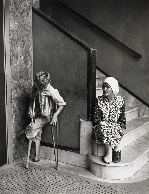 boy on crutches at left, with stump in place of proper right foot and proper left lower leg missing; woman wearing headscarf and flowered dress seated on steps at right