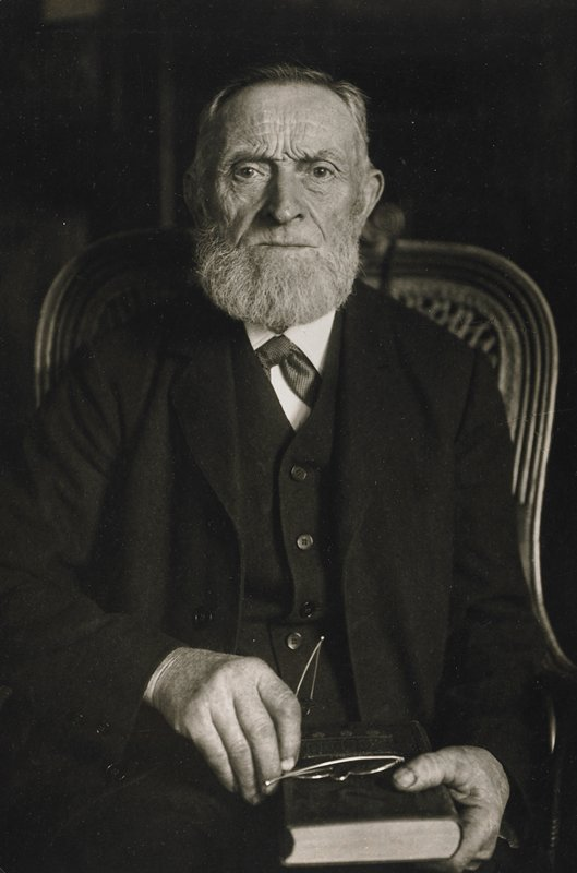 seated bearded man dressed in black holding book and glasses